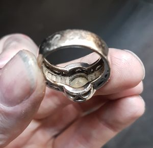Dirt underneath the settings in a ring